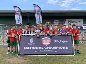 Coventry Utd and Peterborough under-11's take a picture with the National Champions banner